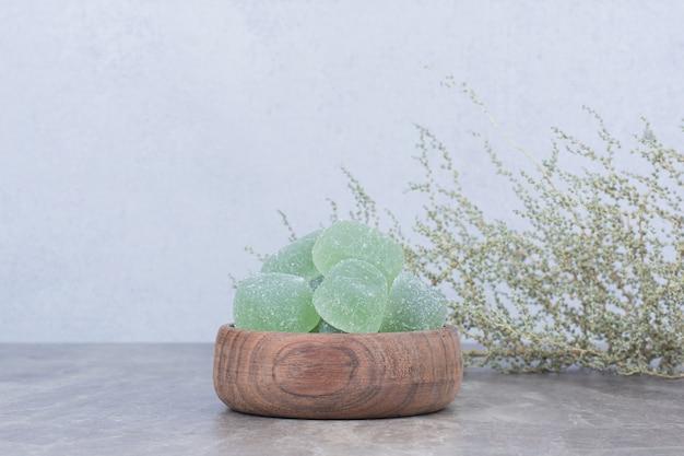 Чаша мармеладных конфет на каменном столе.