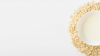 Bowl of milk over the heap of muesli on white background