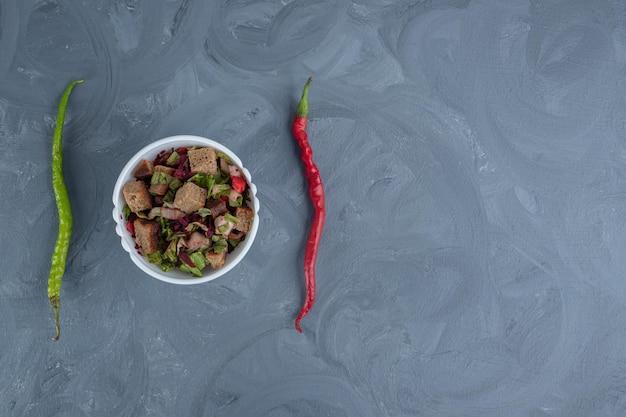 大理石のテーブルの上の2つのコショウの真ん中にミックスサラダのボウル。