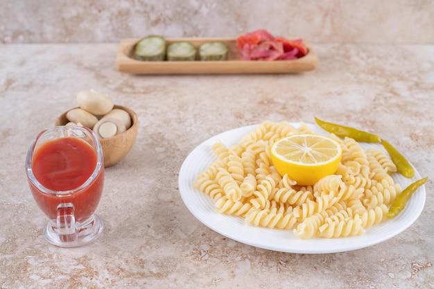 Чаша с грибами, поднос с закусками из солений, основное блюдо из макарон и заправка из кетчупа на мраморной поверхности.