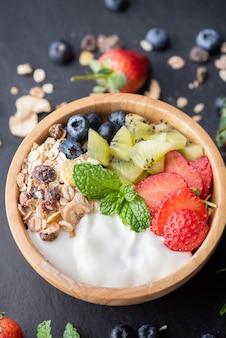 ヨーグルト、新鮮なブルーベリー、イチゴ、キウイ ミント、ナッツの入ったオーツ麦のグラノーラ ボウルで、ヘルシーな朝食、ヘルシーな朝食メニューのコンセプト。黒い岩の上
