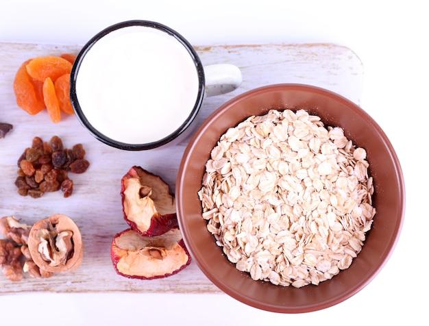 Чаша овсянки, кружка йогурта, курага и грецкие орехи на деревянной разделочной доске, изолированной на белом
