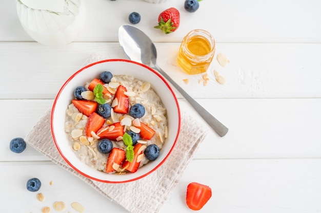 Чаша овсяной каши с черникой, клубникой, миндальными лепестками и медом на белом деревянном фоне. здоровая пища на завтрак, вид сверху, копией пространства.