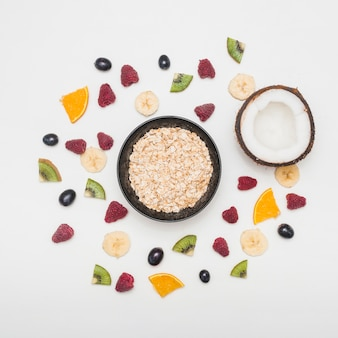 Bowl of oats and halved coconut spread with raspberries; grapes; banana; kiwi slices on white background
