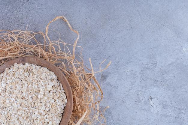 大理石の表面の装飾的なわらの山の上に置かれたオーツ麦のボウル