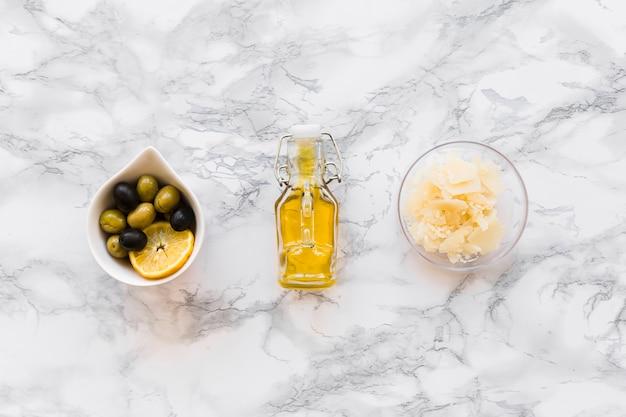 大理石の背景にオイルボトルとオリーブとチーズのボウル