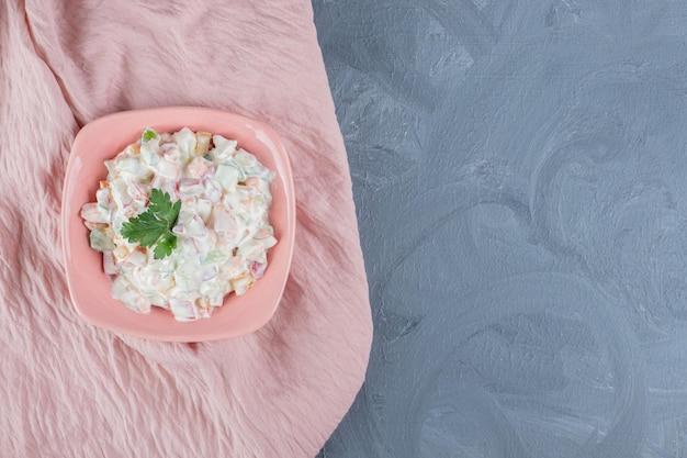 Чаша салата оливье, украшенная листьями петрушки на розовой скатерти на мраморном столе.