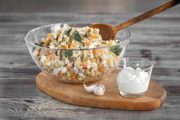 Чаша традиционного салата оливье, микс нарезанных отварных овощей и мяса