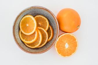 Bowl of orange slices on white