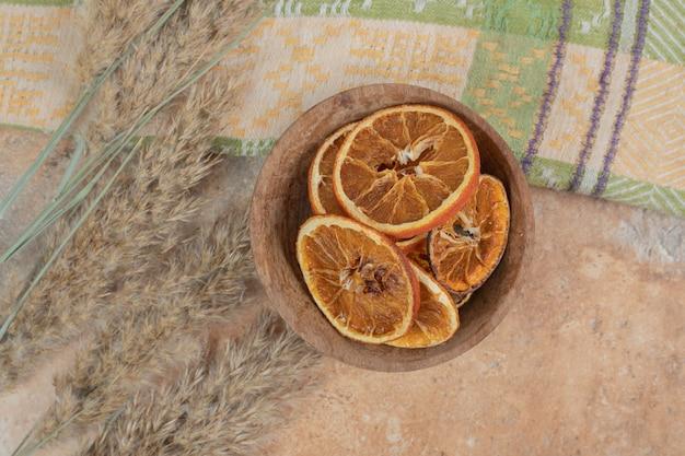 Чаша апельсиновых дольок со скатертью на мраморной поверхности.
