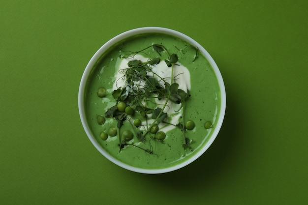 緑の表面にエンドウ豆のスープのボウル
