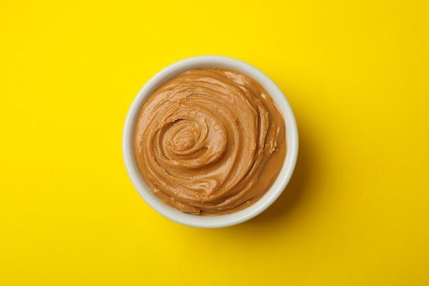 Чаша арахисового масла на желтом фоне, вид сверху