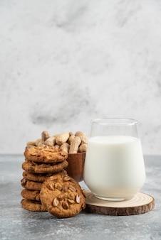 ピーナッツのボウル、牛乳のガラス、大理石のテーブルに有機ピーナッツとクッキー。