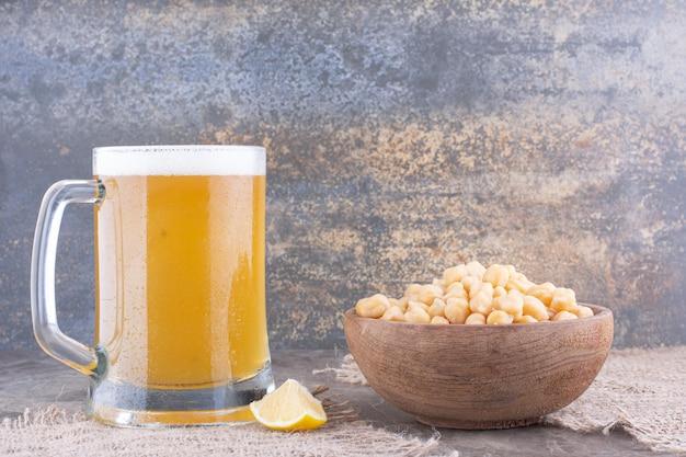 완두콩과 대리석 테이블에 맥주 한 잔의 그릇. 고품질 사진