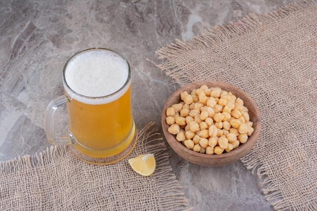 大理石のテーブルにエンドウ豆のボウルとビールのグラス。高品質の写真