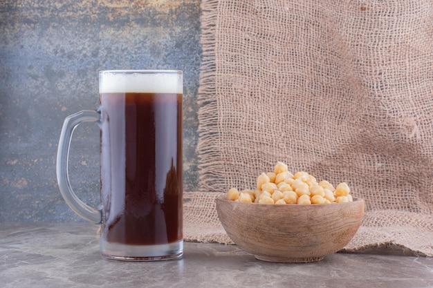 大理石のテーブルにエンドウ豆のボウルとダークビールのグラス。高品質の写真