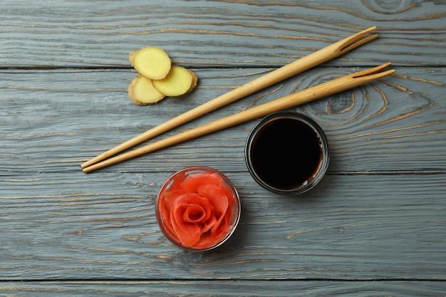 木製のテーブルに生姜のピクルス、醤油、箸のボウル