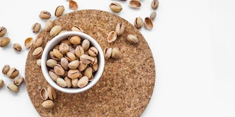 Bowl of pistachio nuts on cork round board against white background