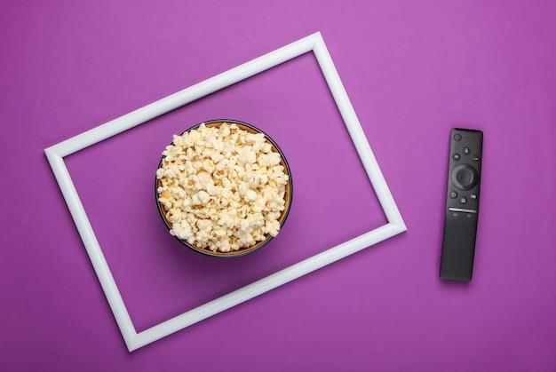 白いフレームと紫色の表面にポップコーンとテレビのリモコンのボウル