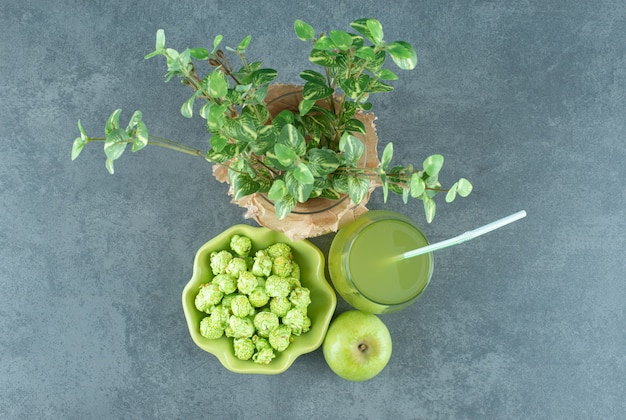 ポップコーンキャンディーのボウル、リンゴジュースのグラス、単一のリンゴ、大理石の背景に装飾的な植物が付いた包まれたワセ。高品質の写真