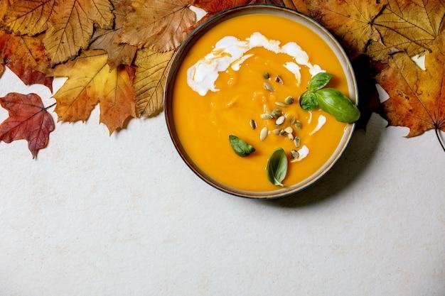 Чаша вегетарианского крем-супа из тыквы или моркови, украшенная свежим базиликом