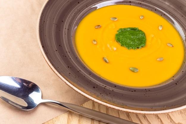 素朴な木製の背景にカボチャのスープのボウル。