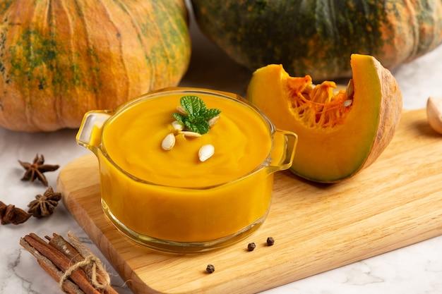 Чаша тыквенного супа на деревянной разделочной доске