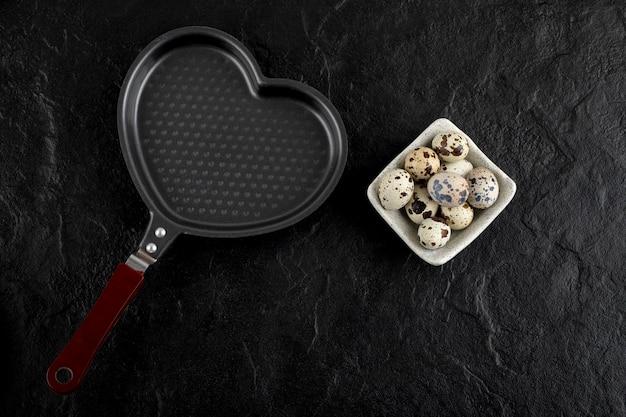 Миска перепелиных яиц вокруг пустой кастрюли в форме сердца.