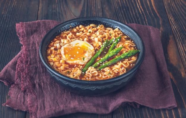나무 탁자에 반숙 계란과 아스파라거스를 넣은 라면 한 그릇