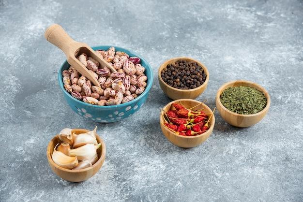 원시 콩 및 대리석 배경에 향미료의 그릇.