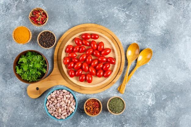 원시 콩, 토마토, 대리석 배경에 향신료의 그릇.