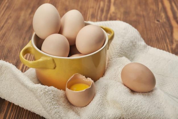 나무 배경에 원시 닭고기 달걀의 그릇