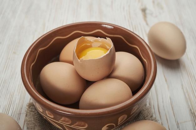 Чаша сырых куриных яиц на деревянных фоне