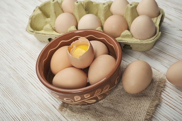 木製の背景に生の鶏卵のボウル