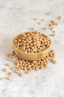白いテーブルの上の生の乾燥ひよこ豆のボウルをクローズアップ