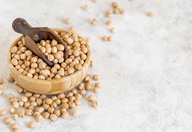 白いテーブルの上にスクープと生の乾燥ひよこ豆のボウルをクローズアップ