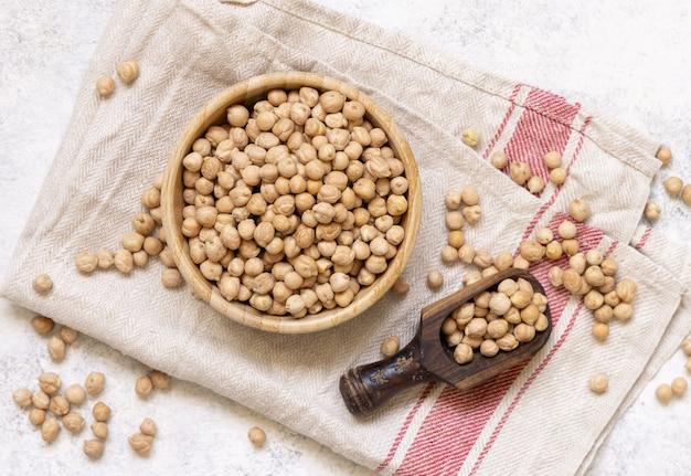 キッチンタオルの上にスクープトップビューの生の乾燥ひよこ豆のボウル