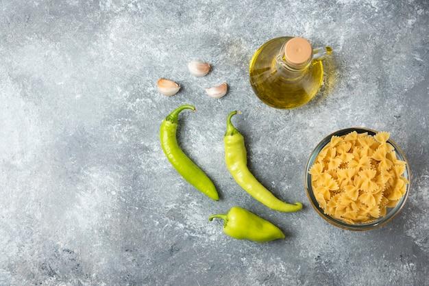 大理石の背景にオリーブオイルと野菜のボトルと生のファルファッレパスタのボウル。