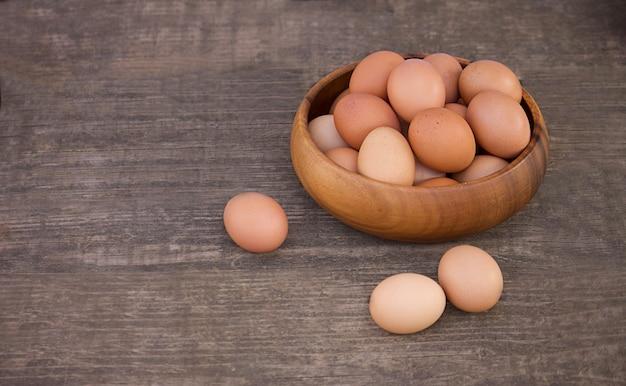 나무 배경에 원시 신선한 갈색 유기농 계란 그릇