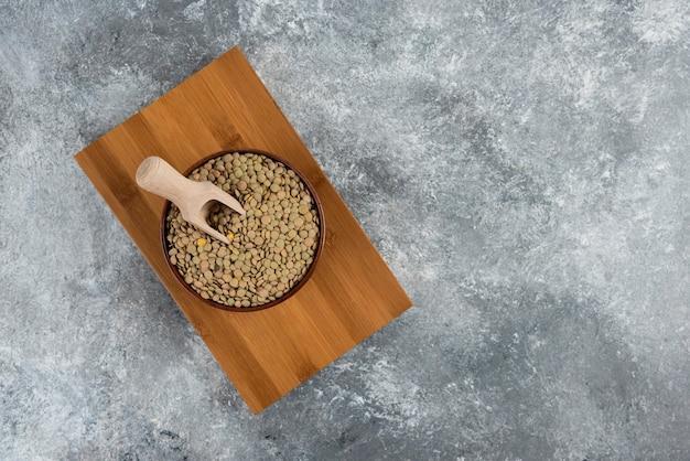 木の板の上に置かれた生の分割エンドウ豆のボウル。