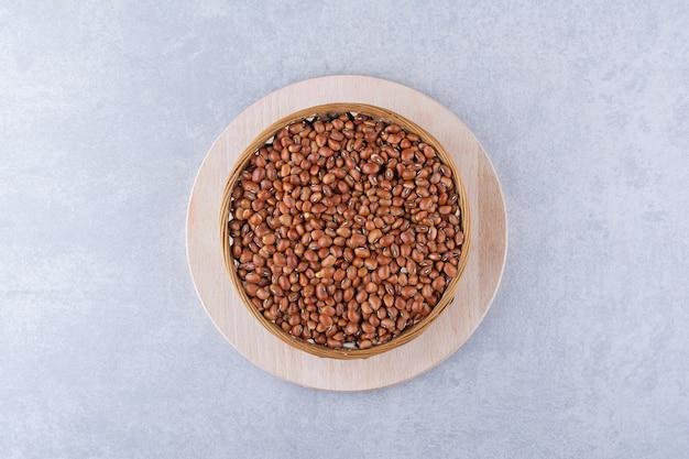 大理石の表面の木製の大皿に置かれた小豆のボウル