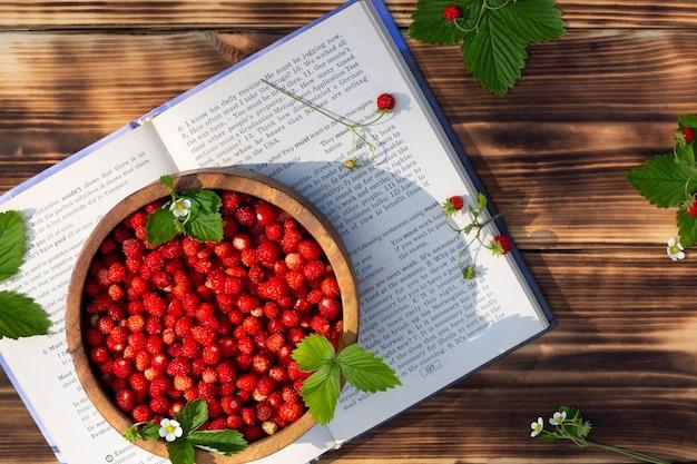 木製の背景の本の上に赤い熟した野生のイチゴと花のボウル