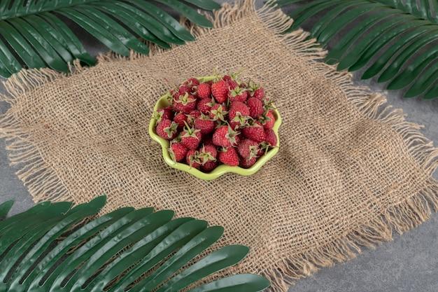 Чаша красной клубники на мешковине с листьями. фото высокого качества