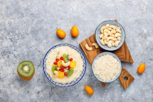キウイスライス、ザクロの種子、金柑、カシューナッツ、上面と米フレークのお粥のボウル