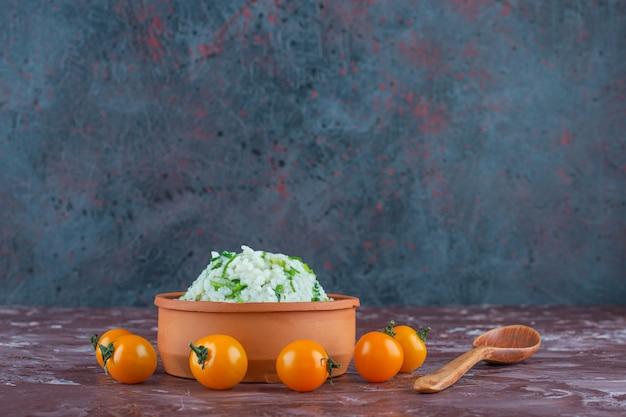 Чаша с рисом, помидорами и ложкой на мраморной поверхности