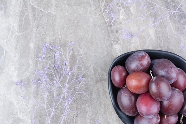 石の背景に熟した梅のボウル。