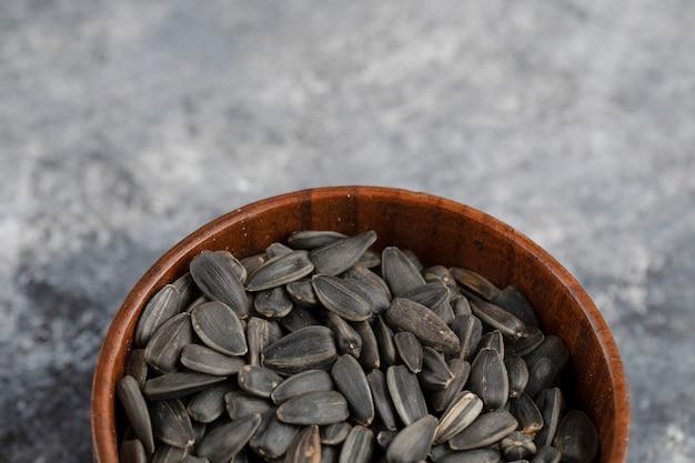 흰색 표면에 볶은 검은 해바라기 씨앗의 그릇