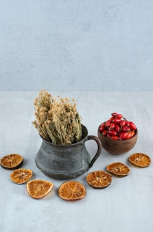 ローズヒップのボウル、乾燥したオレンジと石の表面のrue。