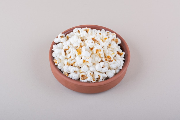 白い背景の上の映画の夜のための塩味のポップコーンのボウル。高品質の写真