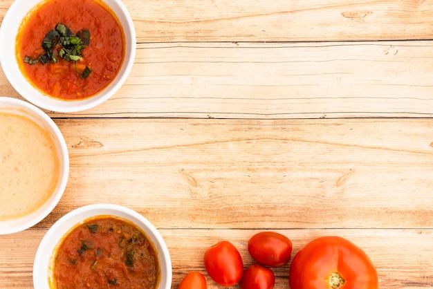 나무 테이블에 소스와 신선한 토마토의 그릇